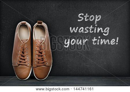 Stop wasting your time text on black board and shoes