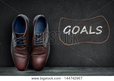 Goals text on black board and business shoes on wooden floor
