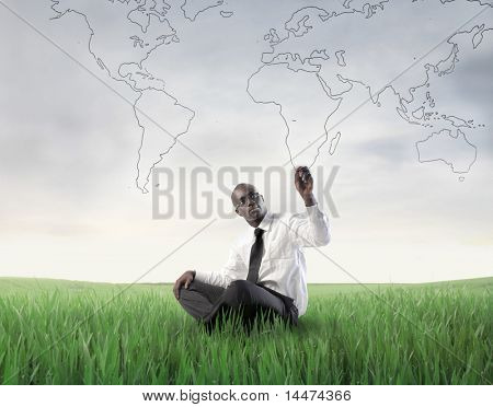 African businessman sitting on a green meadow and drawing a world map