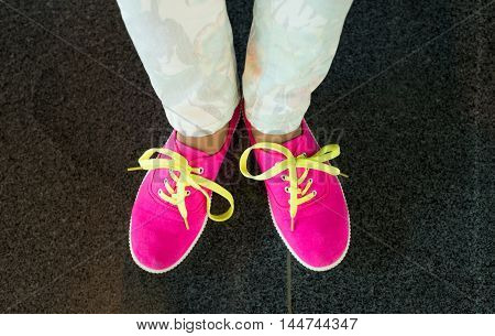 Pink sneakers with yellow shoes lace on girl young woman legs outdoors on black marvel flloor