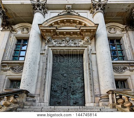 Berlin- Germany - AUGUST 10 2015: Beautiful metal door engraved at the endo of a stone stairs between two marble columns of a great building main facade.