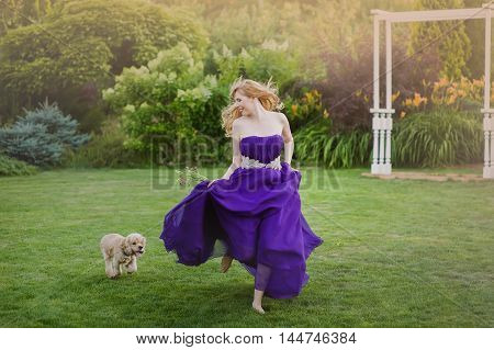 Beautiful girl running on lawn with dog. Bridesmaid in a purple evening gown.