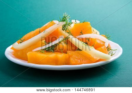 Orange Tomato On A Plate With Onions On A Green Background