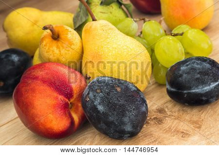 a few fresh bio pears plums grapes and nectarine on the wooden table