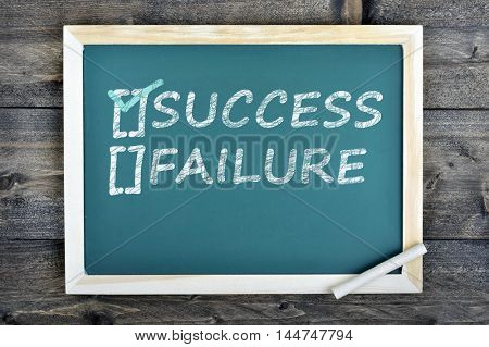 Success text on school board and chalk on wooden table