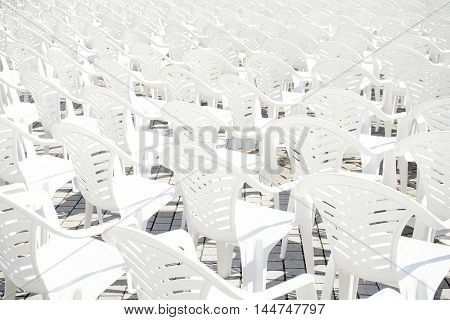 Abstract image of a bunch of white plastic deck chairs