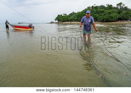 Labuan,Malaysia-Aug 28,2016: Group of fisherman with the fisherman boat and fishing net at Kiansam beach,Labuan island.Fishing is one of the occupations of people in Labuan Pear Of Borneo,Malaysia.