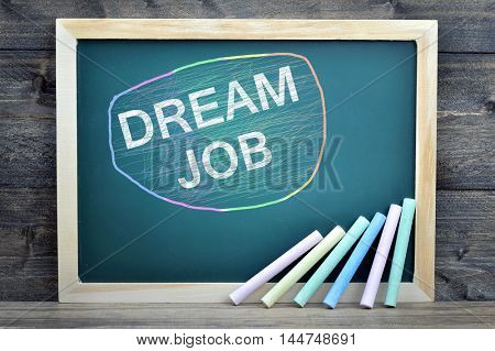 Dream Job text on school board and chalk on wooden table