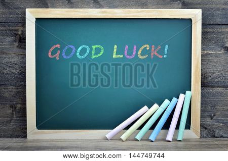 Good Luck text on school board and chalk on wooden table