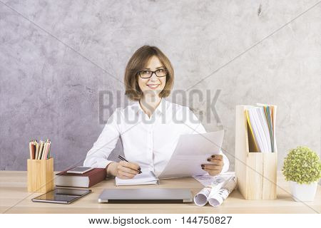 Happy businesswoman doing paperwork at messy office desktop with electronic devices and other items on concrete wall background