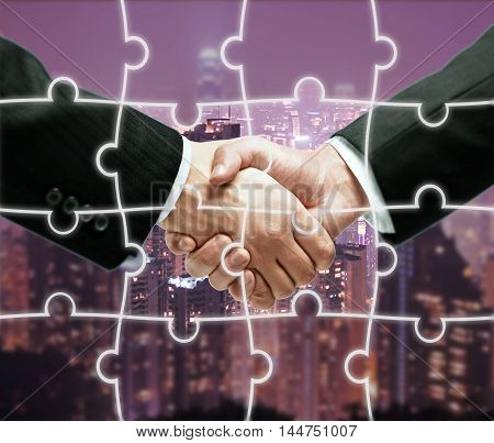 Businesspeople shaking hands on night city background with puzzle piece pattern. Teamwork concept