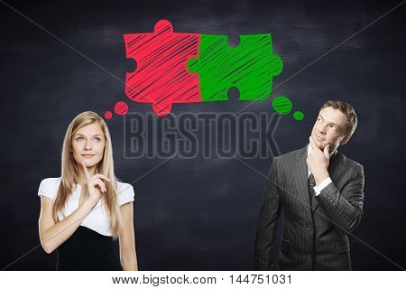 Young businessman and businesswoman thinking about putting colorful puzzle pieces together on blackboard background. Teamwork and partnership concept