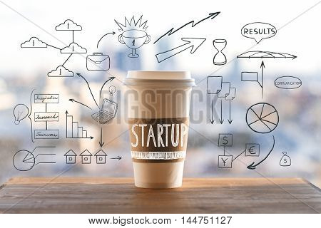 Start up concept with take away coffee cup and abstract business drawings on wooden desktop and blurry city view background