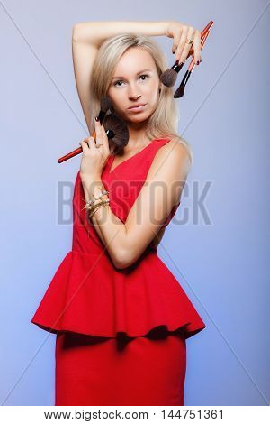 Cosmetic beauty procedures and makeover concept. Attractive woman red dress holds makeup professional brushes near face. Make-up applying with accessories tools. Blue background