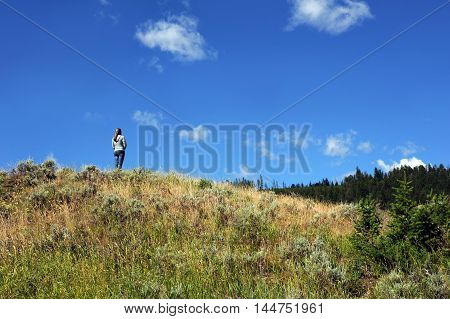 Young woman stands alone on a hillside admiring the vastness of Yellowstone National Park in Wyoming. She is wearing jeans and a grey jacket.