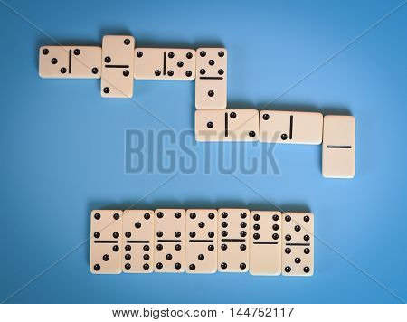 Group of dominoes on background of blue artist paper