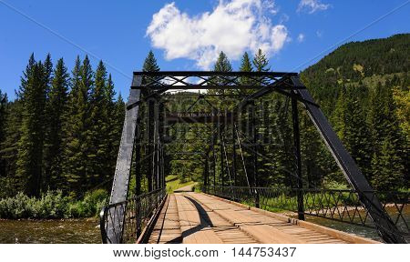 Black steel bridge spans the Gallatin River. Sign on bridge calls it the