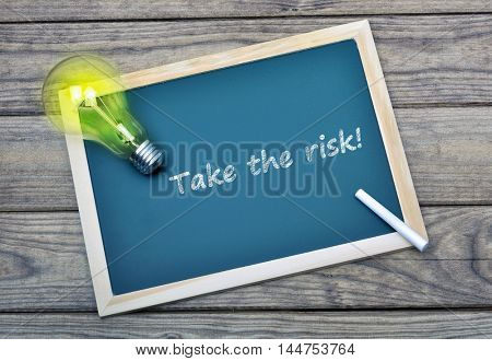 Take the risk text on school board and glowing light bulb