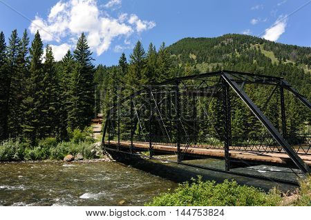 Black steel bridge spans the Gallatin River in Montana. Road continues on to homeplace with cabin. Gallatin Range in the Rocky Mountains rises behind forest.