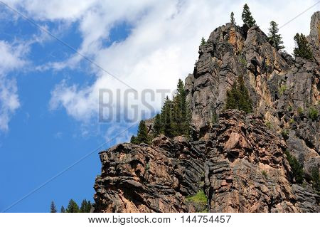 Rugged Gallatin Range climbs skyward as soft clouds form over pinacle. Sturdy fir trees cling to rocky perches.