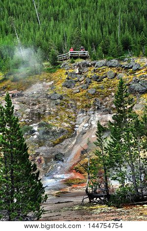 Perched on ridge overlooking thermal hot springs visitors stand on viewing deck in Yellowstone National Park.