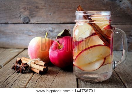 Autumn Themed Detox Water With Apple, Cinnamon And Red Pear In A Mason Jar On A Rustic Wood Backgrou