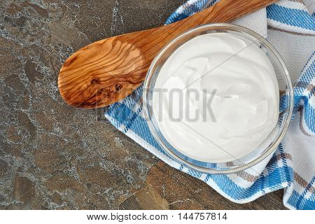 Bowl Of Healthy Greek Yogurt, Downward View With Spoon And Cloth Against A Stone Background