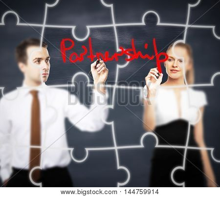 Business man and woman writing partnership on abstract blackboard background with puzzle piece pattern