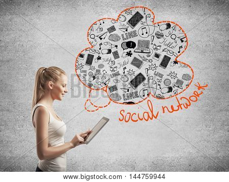 Side view of young woman using digital tablet with abstract social network sketch on concrete background