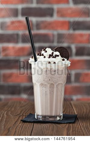 Chocolate cookies and cream, milk chocolate cocktail in a tall glass on a wooden background
