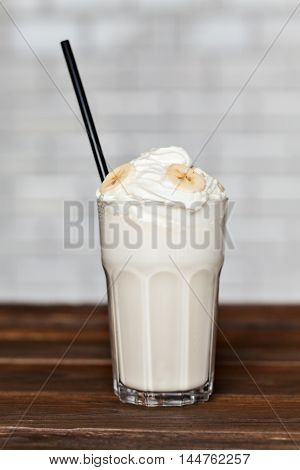 Milk cocktail with banana cream in a tall glass on a wooden background
