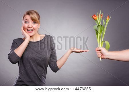 Meeting and date concept. Girlfriend on date getting bouquet of red tulips. Boyfriend hand palm giving tulips gift present to his girl.