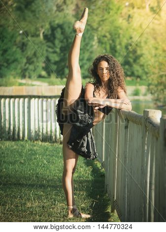 Latin dancer with black clothes lifting her leg and crossing her arms