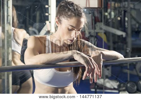 Woman Resting On A Weight Bar.