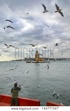 Istanbul Turkey - December 04 2013: European part of Istanbul in the background against the shore. Left Blue Mosque medium Hagia Sophia Topkapi palace dome seem right. The Maiden's Tower (Turkish: Kiz Kulesi) also known as Leander's Tower since the mediev
