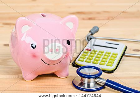 Piggy bank and stethoscope with calculator on wooden background.