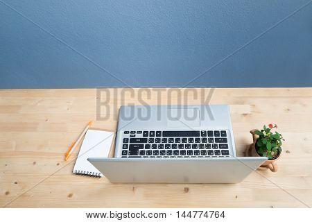 Office desk with laptop Note paper Euphorbia milii flower on terracotta flower pot. View from above notebook keyboard.