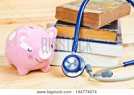 Piggy bank and Stethoscope on book on wooden table closeup