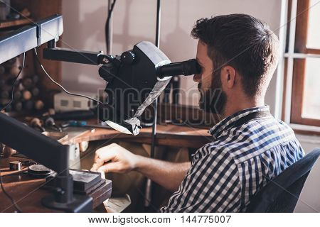 Jeweler sitting in his workshop looking through a large magnifier while doing precision work on a ring
