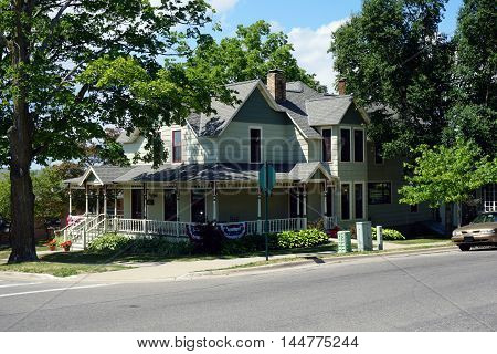 PETOSKEY, MICHIGAN / UNITED STATES - AUGUST 5, 2016: An ellegant Victorian mansion with a wraparound porch on Division Street near downtown Petoskey, Michigan.