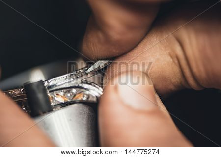 Closeup of a jeweler using tools to shape a silver ring while working at a bench in his workshop