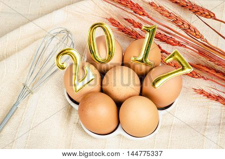 2017 new year number on eggs and whisk with dry wheat.