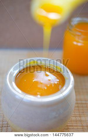Filling a jar of natural tangerine orange juice
