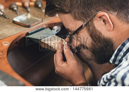 Closeup of a jeweler using a loupe to examine a gem he is working with while sitting at a bench in his workshop
