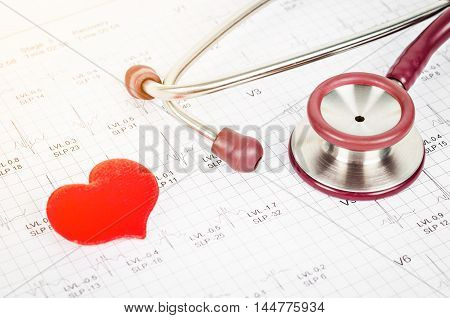 Stethoscope with Red heart on cardiogram report background.