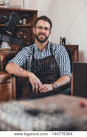 Portrait of a smiling young jeweler in an apron sitting at a bench full of tools in his workshop