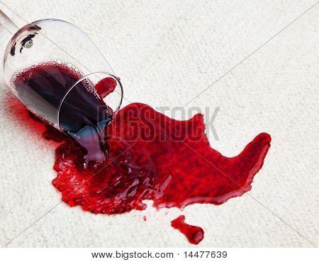 Vino tinto derramado sobre alfombra