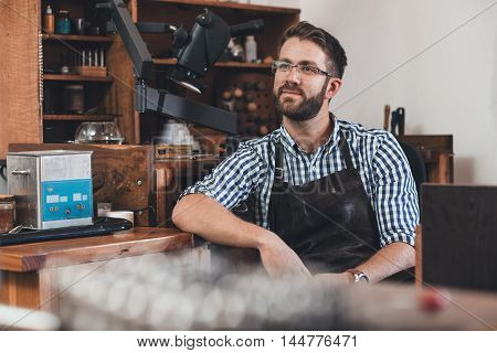 Thoughtful looking young jeweler in an apron sitting at a bench full of tools in his workshop