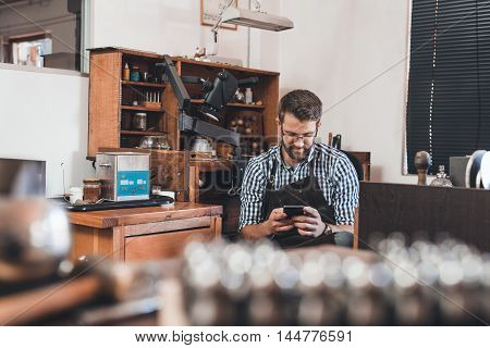 Young jeweler in an apron using a cellphone while sitting at a bench full of tools in his workshop