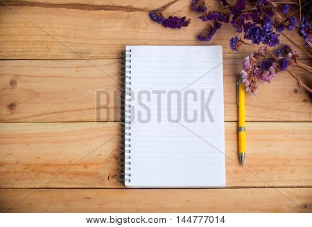 Open empty notebook and yellow pen with dried flower on wooden background warm tone